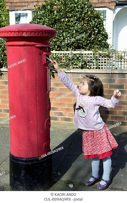 Young girl at post box, reaching up to post letter
