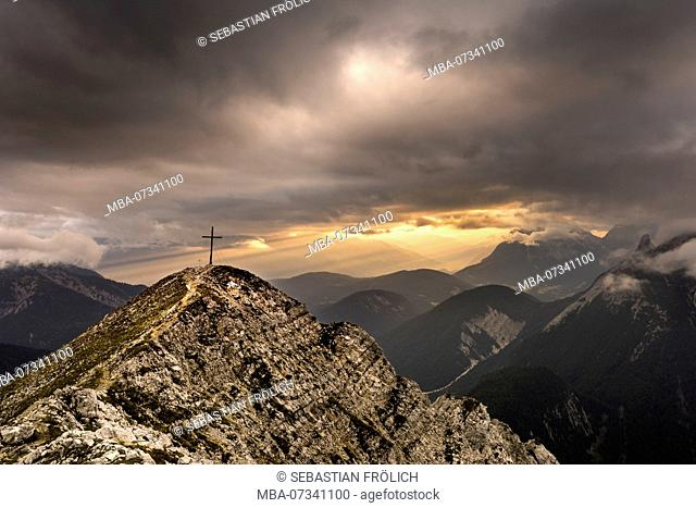 Summit of the Brunnsteinspitze (2179m) with summit cross and in the background light mood in Tyrol, framed by dramatic cloud atmosphere