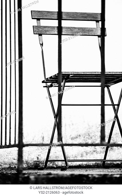 Black and white image of an empty chair on balcony