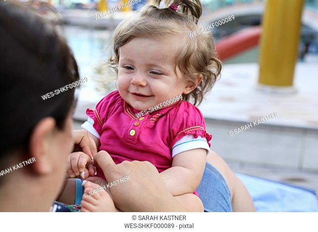 Portrait of smiling baby girl sitting on mother's lap