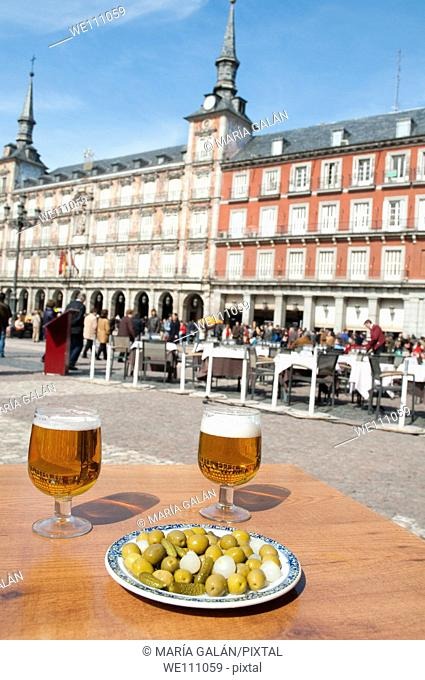 Spanish aperitif: Two glasses of beer and green olives in a terrace. Plaza Mayor, Madrid, Spain