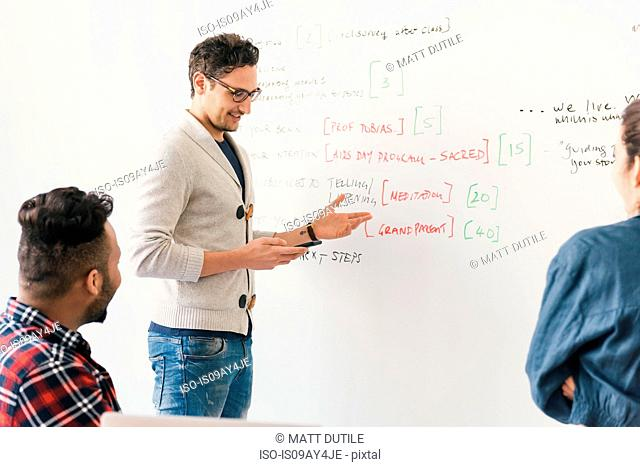 Man in front of whiteboard chatting with colleagues