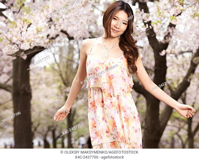 Young smiling happy asian woman in a floral dress at a park with blossoming chery trees in spring