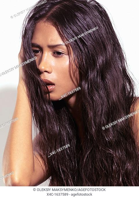 Expressive beauty portrait of a young woman with long brown hair