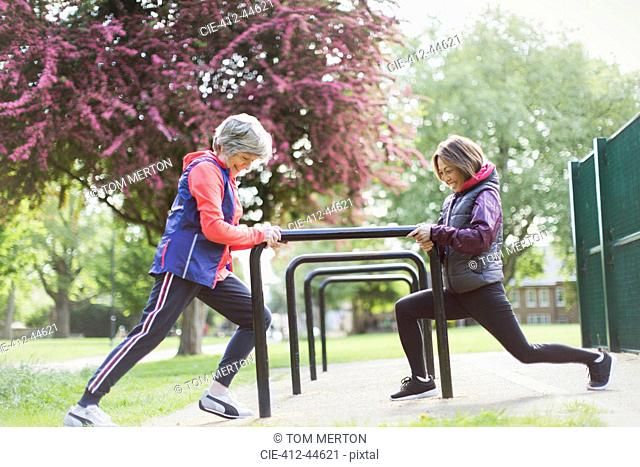 Active senior female runners stretching legs in park