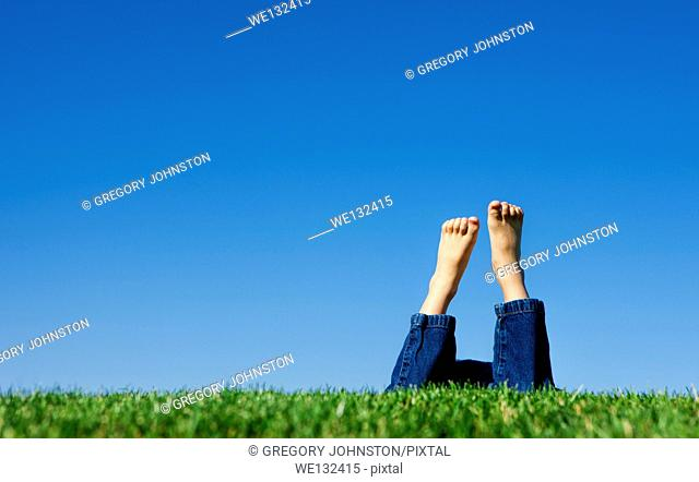 A conceptual image of the feet of a child in the grass shown on a bright summer day against a blue sky