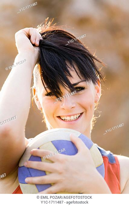 Attractive young woman with a ball