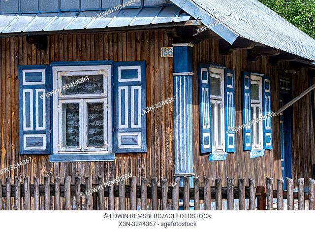 Exterior of cabin-style house adorn with colorful shutters in Trzescianka the 'Land of the Open Shutters', Poland,