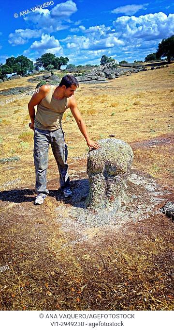 Boar. Alberto showing Vettones sculpture, dehesa of La Mata de Alcántara, Caceres, Extremadura, Spain