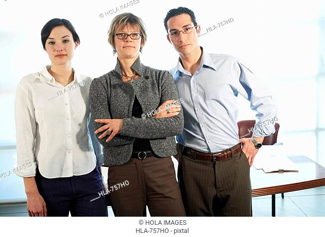 Portrait of two businesswomen and a businessman standing in an office