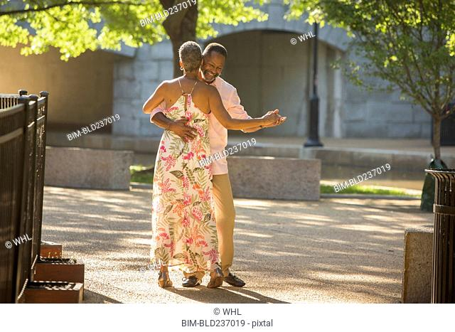 Black couple dancing in park