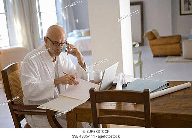 Mature man talking on a mobile phone and looking at a laptop