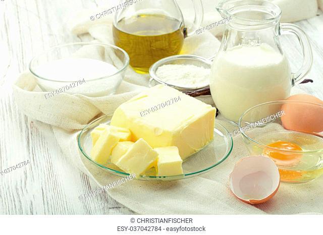 baking ingredients eggs, flour, sugar, butter, vanilla, cream on a background