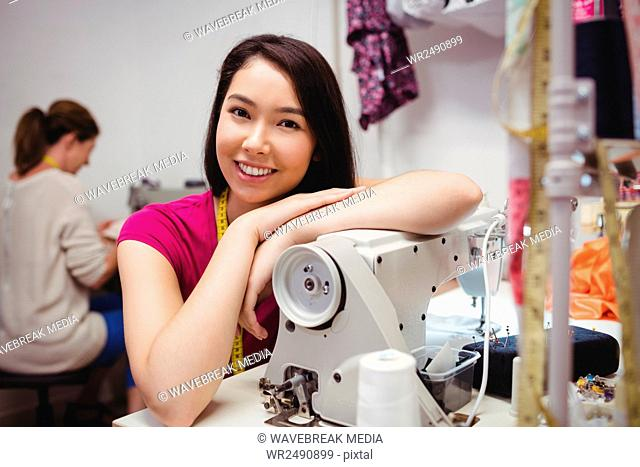 Female dressmaker leaning on sewing machine