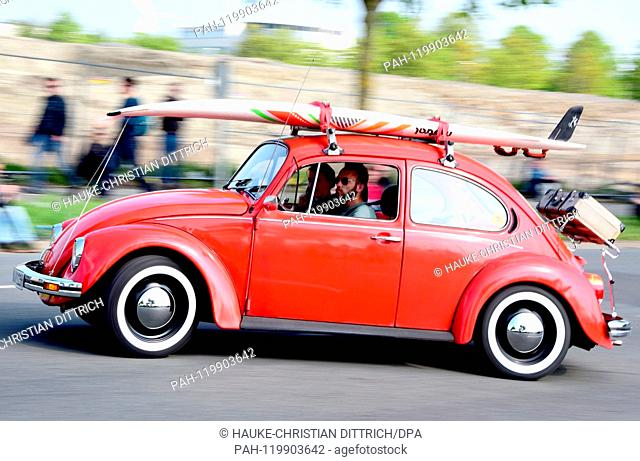 A Volkswagen Beetle with a surfboard on it at the Maikaefertreffen (May Beetle Meeting) in Hanover (Germany), 01 May 2019