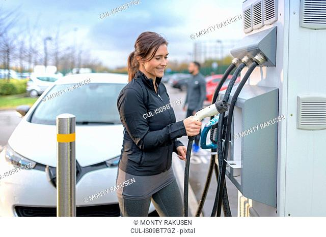 Sportswoman at electric car charging point, Manchester, UK