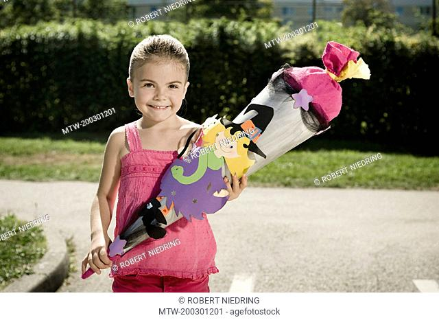 Smiling girl holding school cone