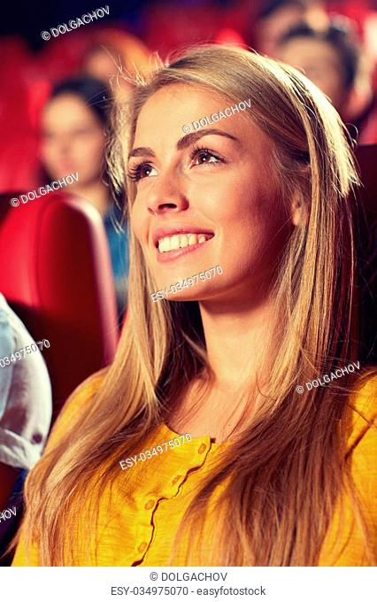 cinema, entertainment and people concept - happy young woman watching comedy movie in theater