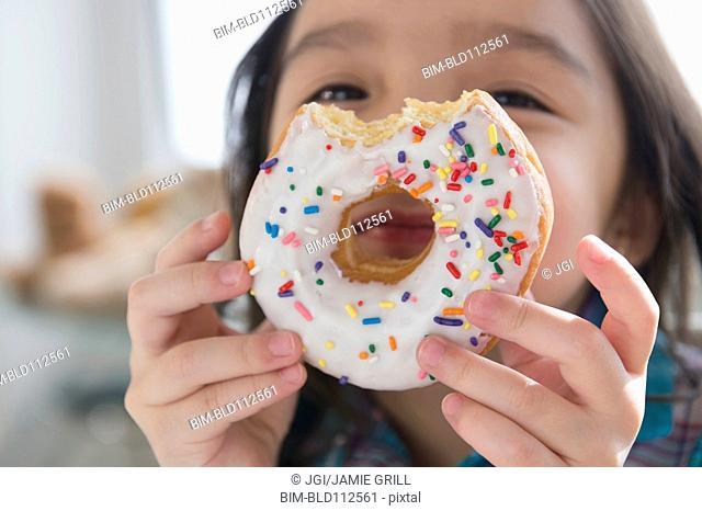 Asian girl peeking through donut hole