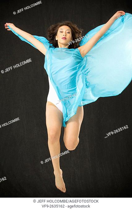 Beautiful young woman dancer in light blue cape and white leotard, jumping with mouth closed and cape unfurled, vertical image
