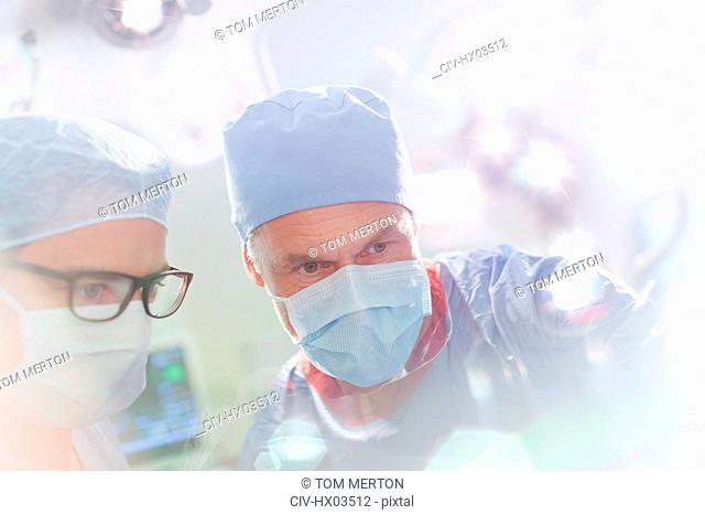 Surgeons wearing surgical mask looking down in operating room