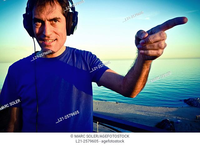 Smiling man with headphones pointing the finger in any direction