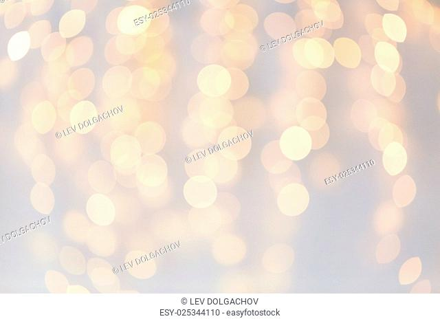 holidays, background and illumination concept - blurred golden christmas decoration or garland lights bokeh