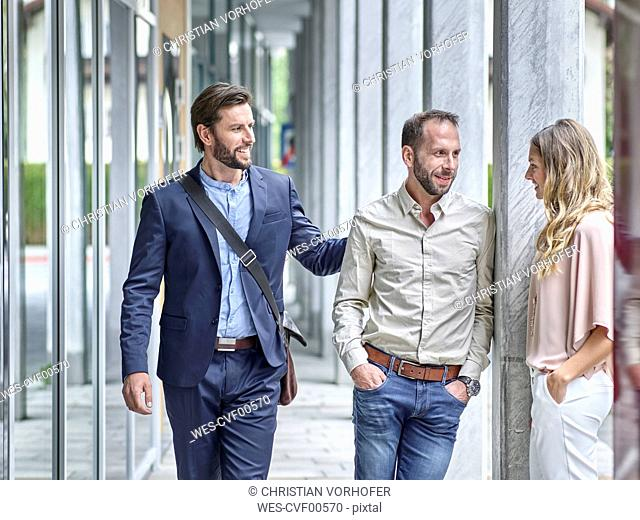 Business people talking outside office building