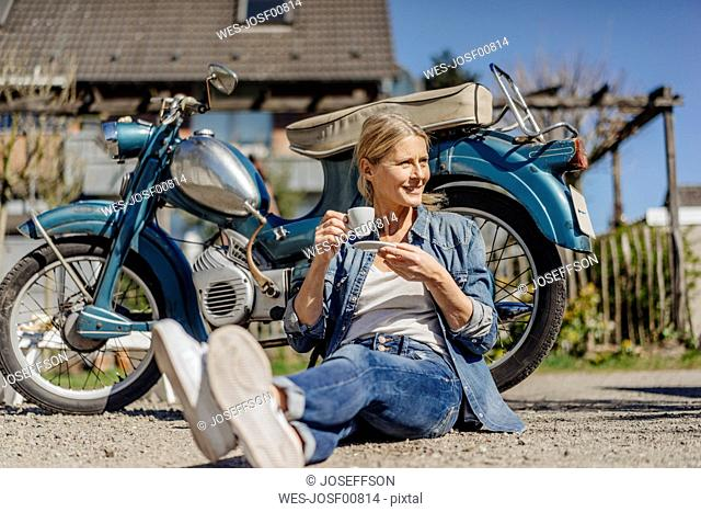 Smiling woman sitting at vintage motorcycle having a coffee break