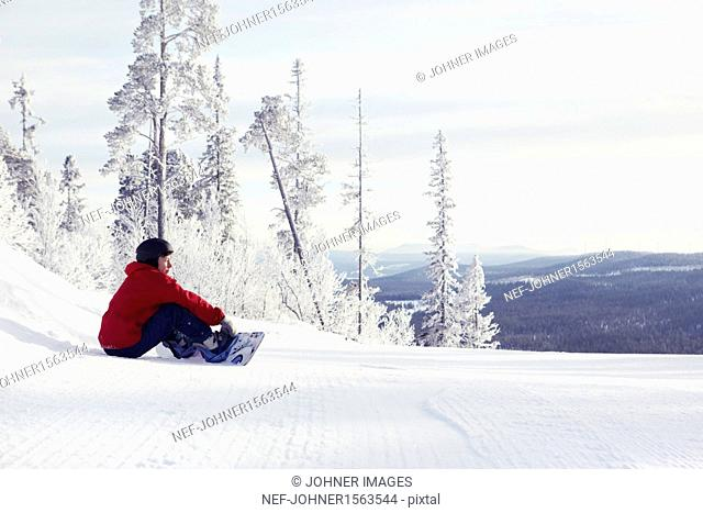 Woman with snowboard sitting and looking at view