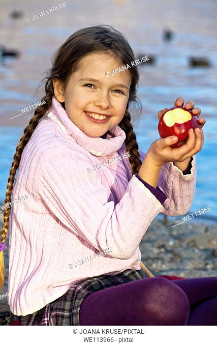 girl is eating an apple on the banks of a lake in autumn