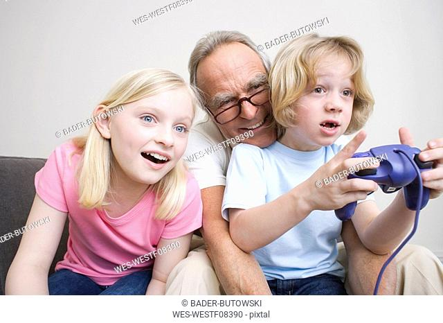 Grandfather and grandchildren 8-9 playing video game, portrait