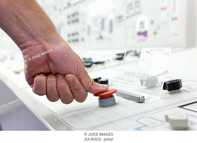 Close up of man pushing red emergency button on control panel
