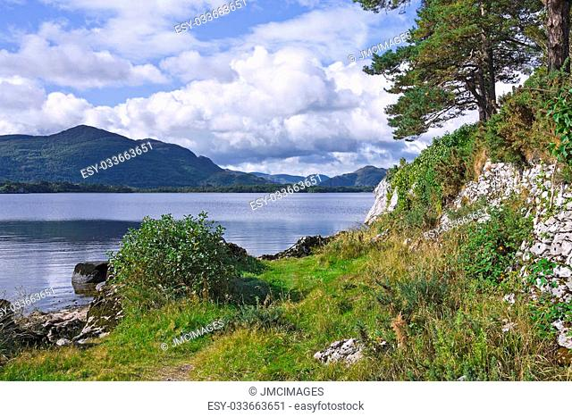 Torc Mountain and the Eagle's Nest Rock from a grassy path by the shore of Lough Leane, the Lower Lake, Killarney, Ireland