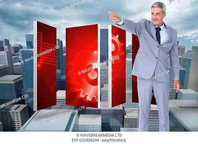 Composite image of handsome businessman pointing away