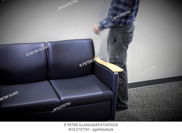 Man standing next to a sofa in a college hallway