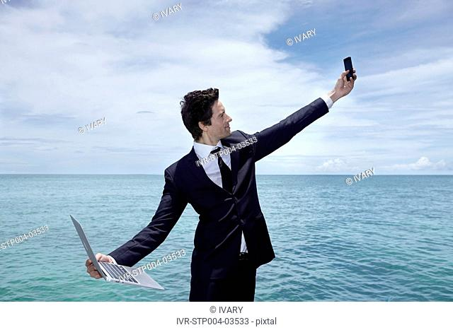 A businessman posing on a dock with a mobile phone and a laptop