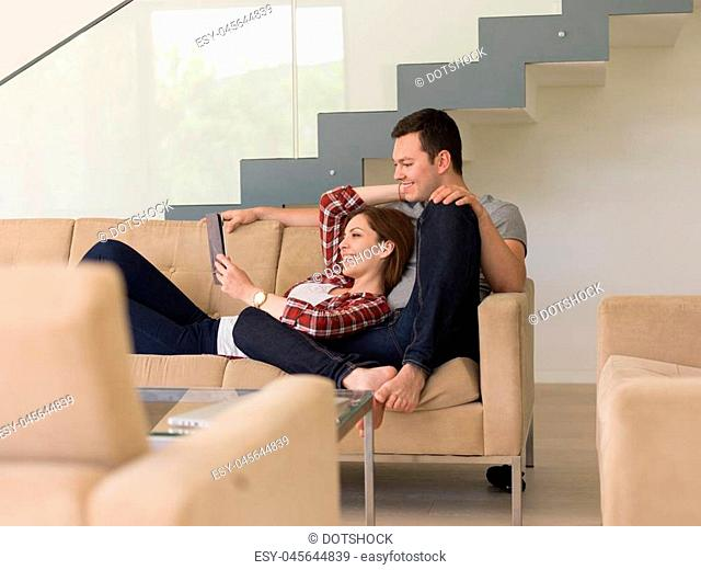 Young couple relaxing at luxurious home with tablet computers reading in the living room on the sofa couch