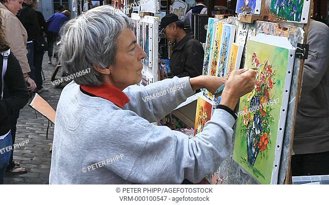 Woman painting at Montmarte in Paris
