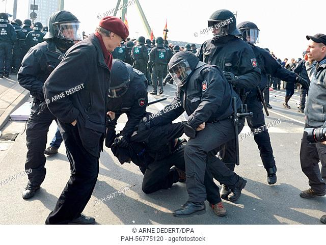 The police overpowers a demonstrator prior to the official opening of the European Central Bank in Frankfurt, Germany, 18 March 2015