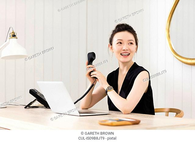 Young woman at desk with telephone handset
