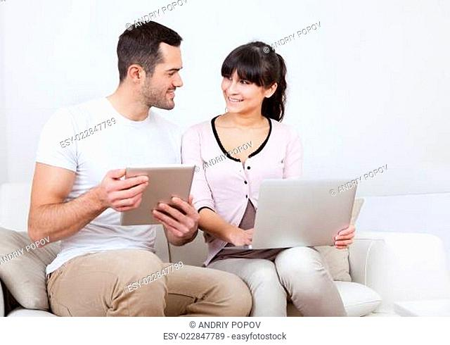 Young couple using laptops in couch