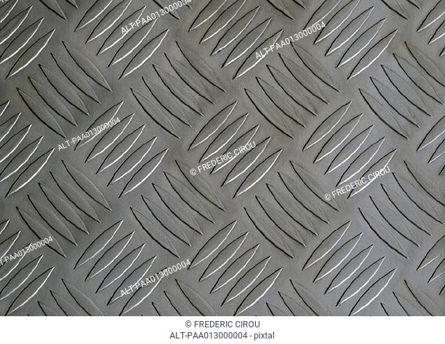 Repetitive pattern on metal plate, close-up, full frame