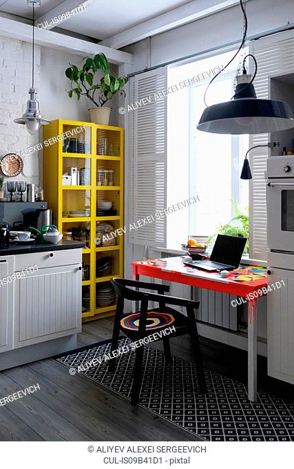 Kitchen with yellow cupboard and laptop on table