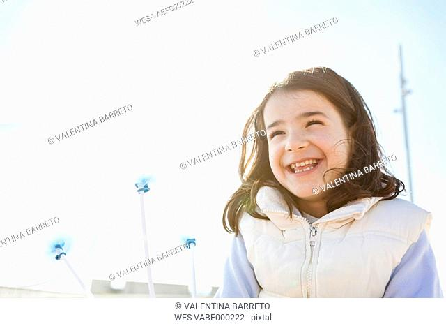Portrait of happy little girl with three transparent balloons
