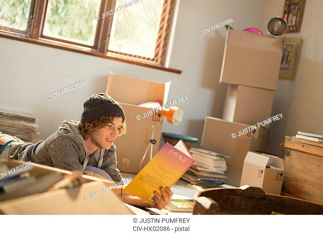 Young man reading book surrounded by moving boxes in apartment