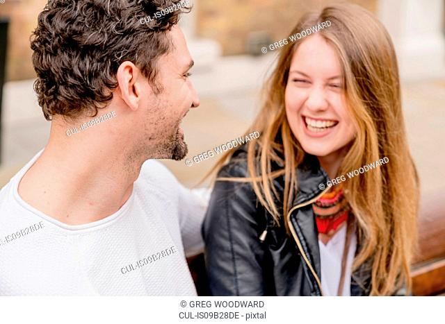 Happy young couple sitting on park bench