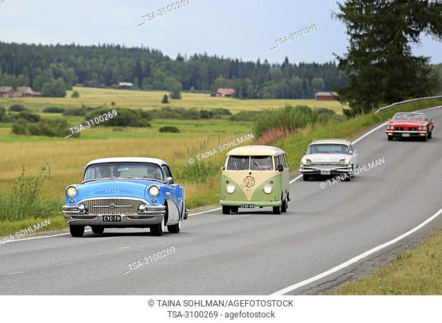VAULAMMI, FINLAND - AUGUST 4, 2018: Classic retro cars and vehicles drive on scenic road on Maisemaruise 2018 car cruise in Tawastia Proper, Finland
