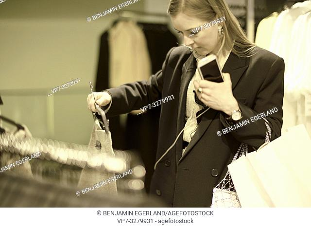 fashionable woman choosing outfit at clothing store, in Paris, France