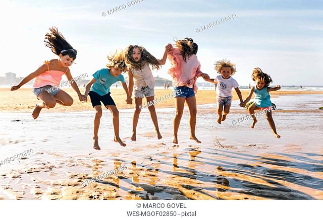 Group of six children jumping in the air on the beach